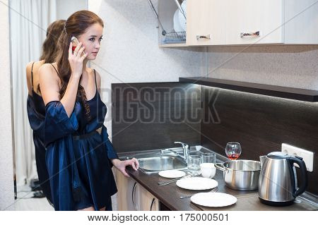 Brunette housewife in blue robe in the kitchen talking on the mobile phone.