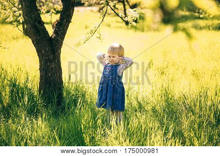 Portrait of happy child standing under huge old apple tree in spring blossoms. Little girl cheerfully playing in garden in countryside. Age of child 2 years and 4 month.