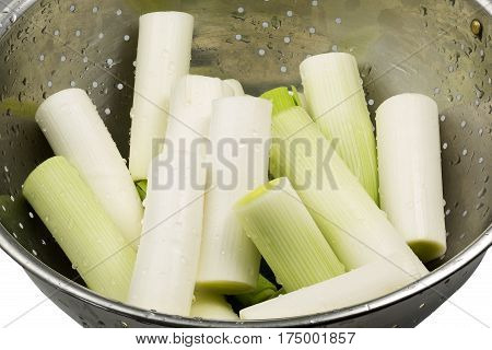 Pieces of fresh leek in a colander with water drops