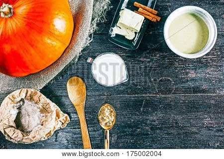 Pumpkin, dough and ingredients for making pancakes on the kitchen desk