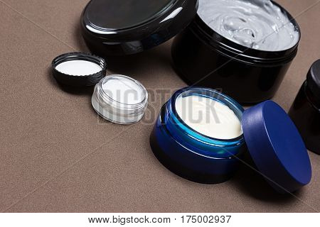 Several open jars of creams. Various skin care cosmetic products. Skincare for men. Oblique angle, copy space