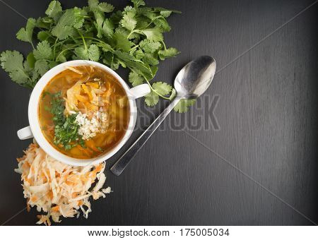 Sour Soup With Cilantro On A Black Background