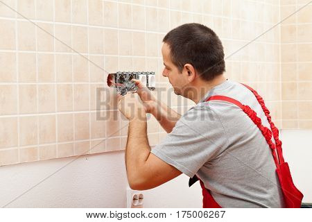 Electrician installing electrical wall fixture - fastening the wires in the receptacle