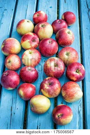 Red apples lie on a blue wooden table