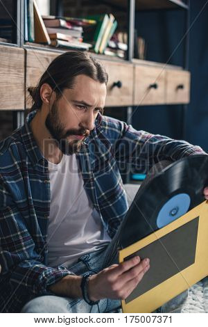 Young bearded man sitting on floor and holding vinyl record