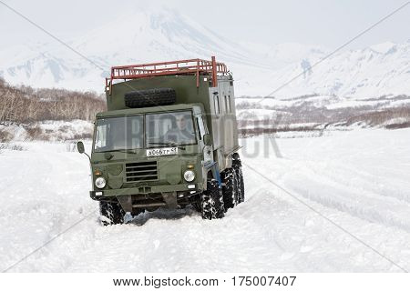 KAMCHATKA PENINSULA RUSSIA - APRIL 4 2014: Old Swedish military off-road vehicle Volvo Laplander C304 (six-wheel drive) khaki color driving in snow along a country road on background volcanoes.
