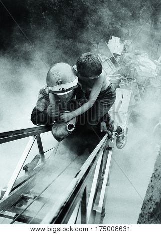 MOSCOW RUSSIA - AUGUST 12, 2002: Firefighter saves a boy from a burning house