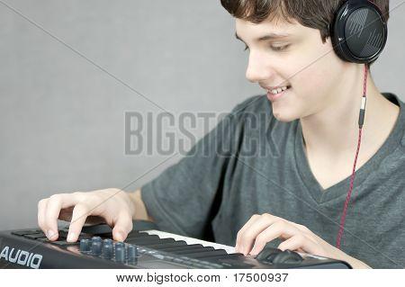 Headphone Wearing Teen Adjusts Keyboard