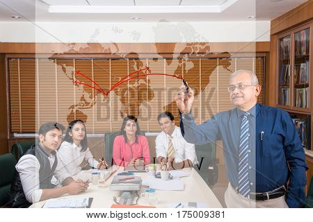 indian senior businessman writing over transparent glass with marker pen giving presentation in meeting room, while other young business people in the background