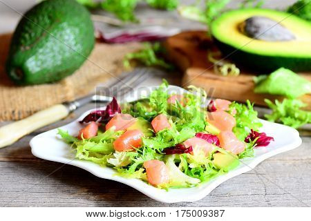 Homemade salad with red fish, lettuce mix, avocado, olive oil and lemon juice on the plate. Fresh raw avocado, fork on a wooden table. Vintage style. Closeup
