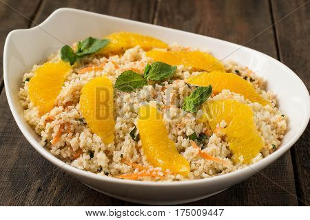 Useful fresh salad of crumbly couscous with carrots orange and mint in a bowl closeup on a wooden table. Dietary vegetarian food traditional Mediterranean cuisine recipes. Selective focus