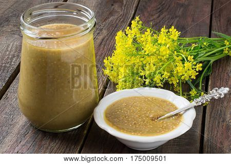 Homemade mustard with grains in jar and gravy boat mustard flowers on old wooden table. Spicy seasoning for various dishes. Selective focus