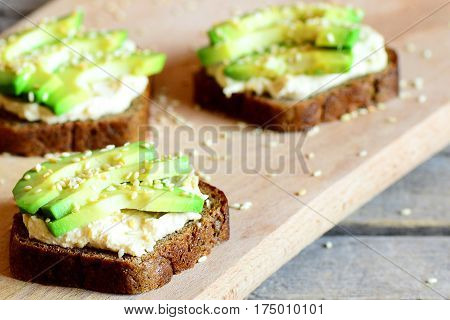Vegan avocado and hummus sandwiches on a wooden board. Quick and healthy open sandwiches. Healthy eating. Meatless meal. Closeup