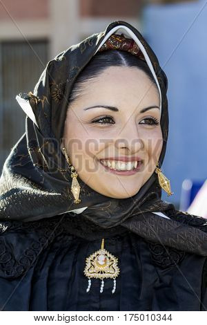 CAGLIARI, ITALY - May 1, 2016: 360 Feast of Saint Efisio - portrait of a beautiful smiling girl parading in traditional Sardinian costume - Sardinia