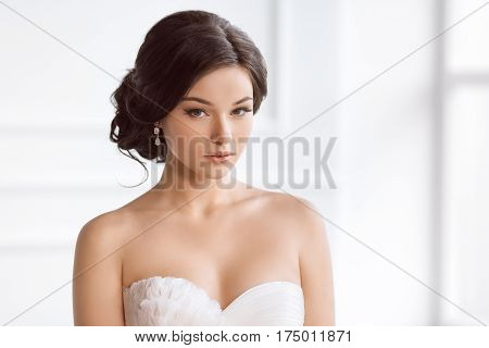 Beauty portrait of bride wearing fashion wedding dress with feathers with luxury delight make-up and hairstyle, studio indoor photo. Young attractive multi-racial Asian Caucasian model. Serious sensual beautiful young woman like a bride in white room at h
