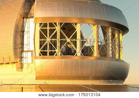 Close up of Gemini observatory with open wind vents on Maunakea volcano on the Big Island of Hawaii. Photo lightly desaturated to remove some of the intense reflected color cast from the sunset.