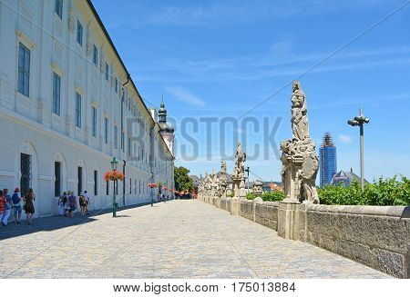 The bridge connects the Prague residence of the Jesuits with the city and the temple of the Chram Sv. Barbory at sunny summer day. St. Anna statue.