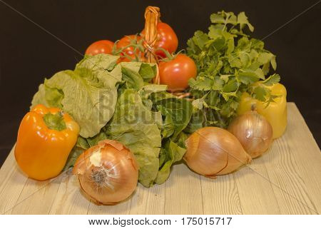 Fresh vegetables : red garden tomatoes, lettuce yellow peppers, parsley, put in small wicker basket put on dark wood table on black background