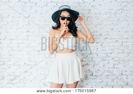 Asian Woman Holding Fingers To Her Lips In Fashionable Dress And Summer Hat Over White Brick Wall -