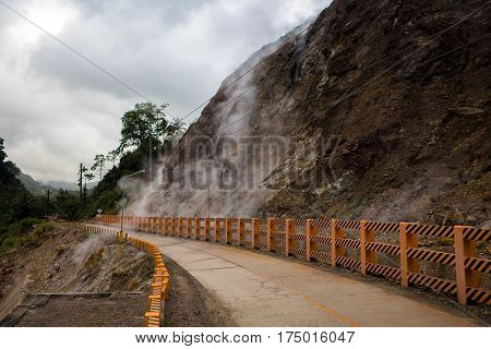 Road near geyser smoke field. Evaporation of gas from rocky mountain. Natural geyser eruption. Hot springs near active volcano. Underground geothermal activity photo. Smoke field in Philippines island