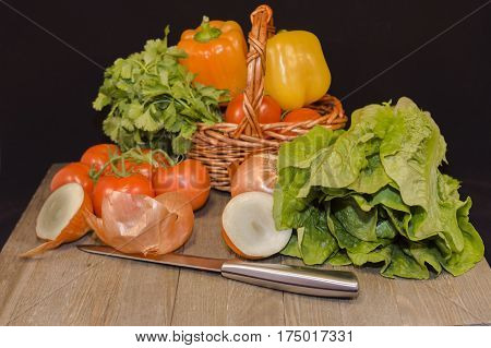 Fresh vegetables : red garden tomatoes, cut twain red onion, yellow peppers, lettuce, parsley, iron knife in small, wicker, basket dark wood ,table ,black, background