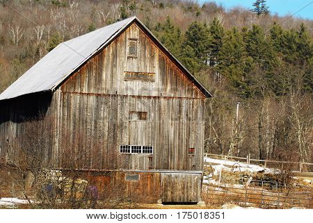 Multi-story wooden New England Barn at the edge of the woods in a field