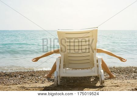 Woman is lying on the sunbed in funny pose. She is tired and enjoy her long-awaited vacation.