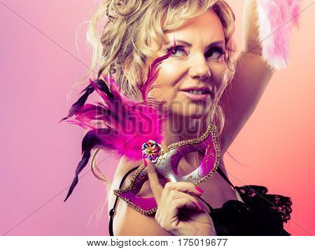 Holidays people and celebration concept. Woman blonde mid aged model holding in hand pink carnival mask feather fan on bright background