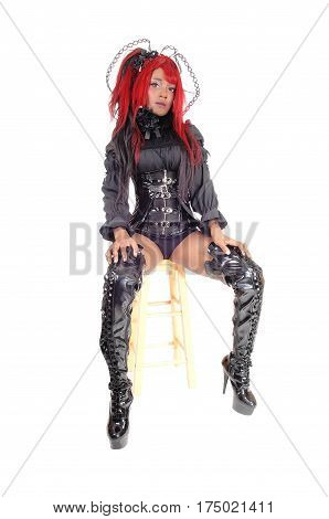 A beautiful African American woman in a black corset panties and long boots with red hair sitting isolated for white background.