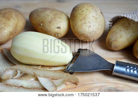 Peeled potato and potato peeler on wooden background