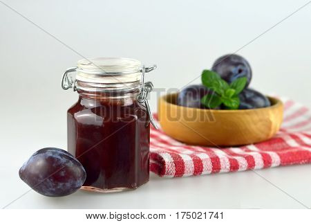 Plum jam in the jar and bowl of fresh plums