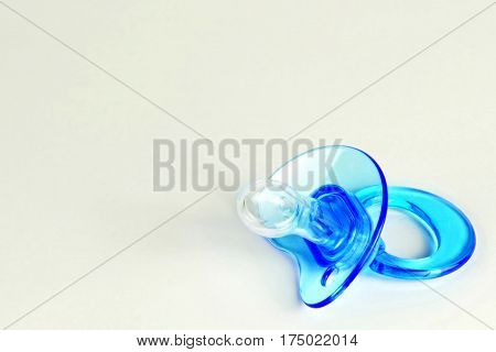 Close up of blue baby soother on light background