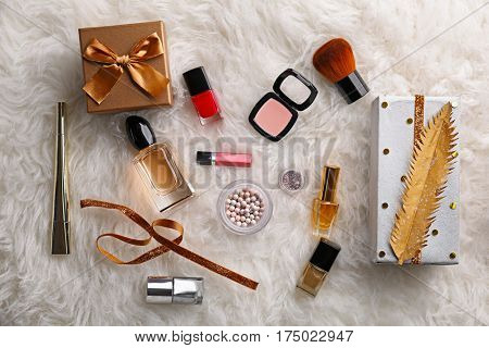 Crafted Christmas gifts and make up cosmetics on furry background