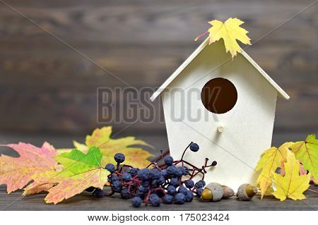 Autumn background: Wooden birdhouse and autumn leaves