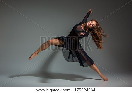 Dancing woman in a black dress. Contemporary modern dance on a gray background. Fitness, stretching model