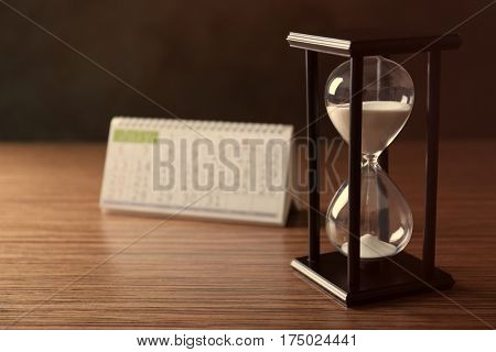 Black hourglass with white sand and calendar on wooden background