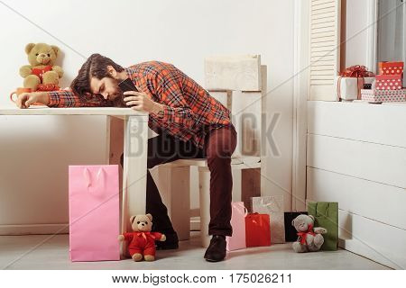 Bearded Man Resting Head On Table With Mobile Phone