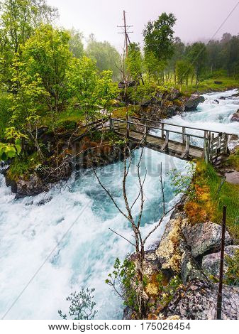 Travel beauty in nature. Small bridge and waterfall torrential river along the Aurlandsfjellet mountains in Norway Sogn og Fjordane foggy hazy summer day