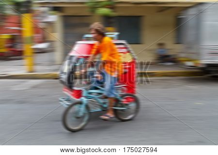 Panning photograph of unidentified man riding Tricycle Taxi. They are often seen in urban-rural fringe area where public transportation services are insufficient and most residents can't afford high commuting costs Philippines
