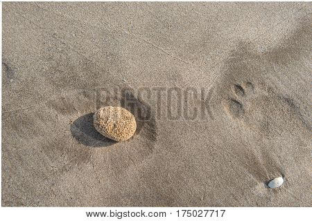 Pebble casting a shadow to the left on the beach sand