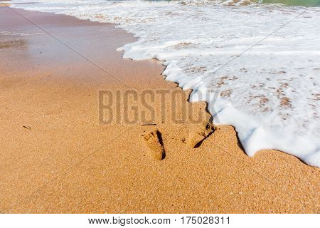 Footprints in sand about to be washed away by incoming wave and sea foam