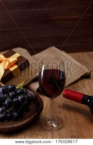 Red wine bottle. Wineglass with dark grapes branch. Gift boxes with bows on rustic wooden background.