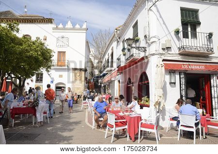 MARBELLA, SPAIN - FEBRUARY 27, 2017: People at outdoors restaurant in Plaza of the Orange Tree in the historic center of Marbella a city of the province of Malaga Andalusia Spain.