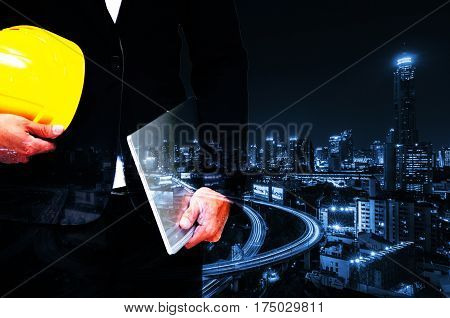 double exposure of professional engineer hold in hand yellow safety helmet and laptop business and industrial concept on night city background, blue color tone effect.