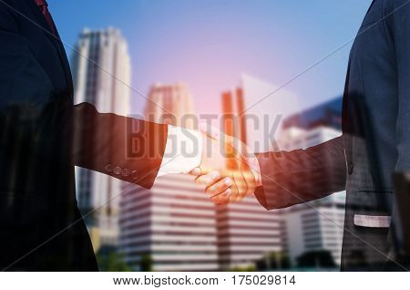 Double exposure of businessman handshake, business concept, successful business meeting  on blurred building business district city background, color tone effect.
