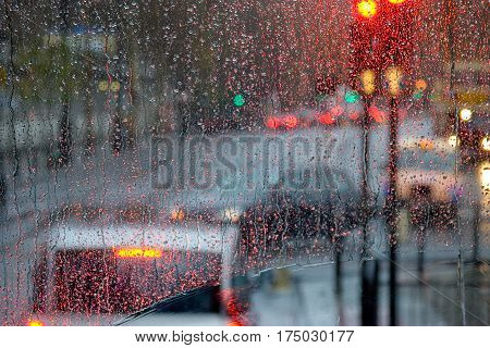 London rain view to red bus through rain-specked window