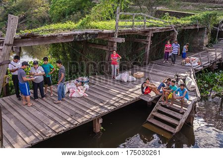 Rio Paraguay, Paraguay on August 5, 2015: Indigenous people make their way to the jetty to trade groceries and welcome their friends. The boat supplies the remote community once a week.