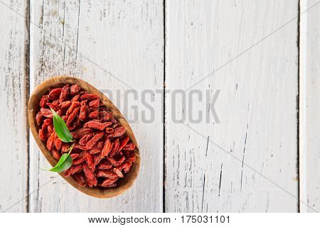 Dry goji berry on old white wooden background, close-up.