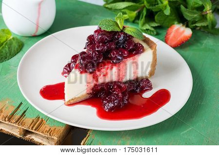 Slice of cheesecake with cranberry sauce decorated with mint leaf on a white plate