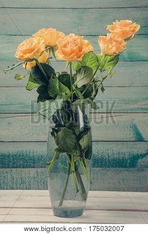 Bouquet of yellow roses in glass vase over old wooden background